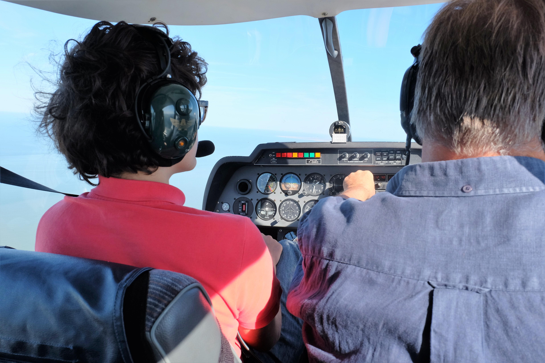 Un jeune miraud volant aux commande en vol de formation avec son instructeur