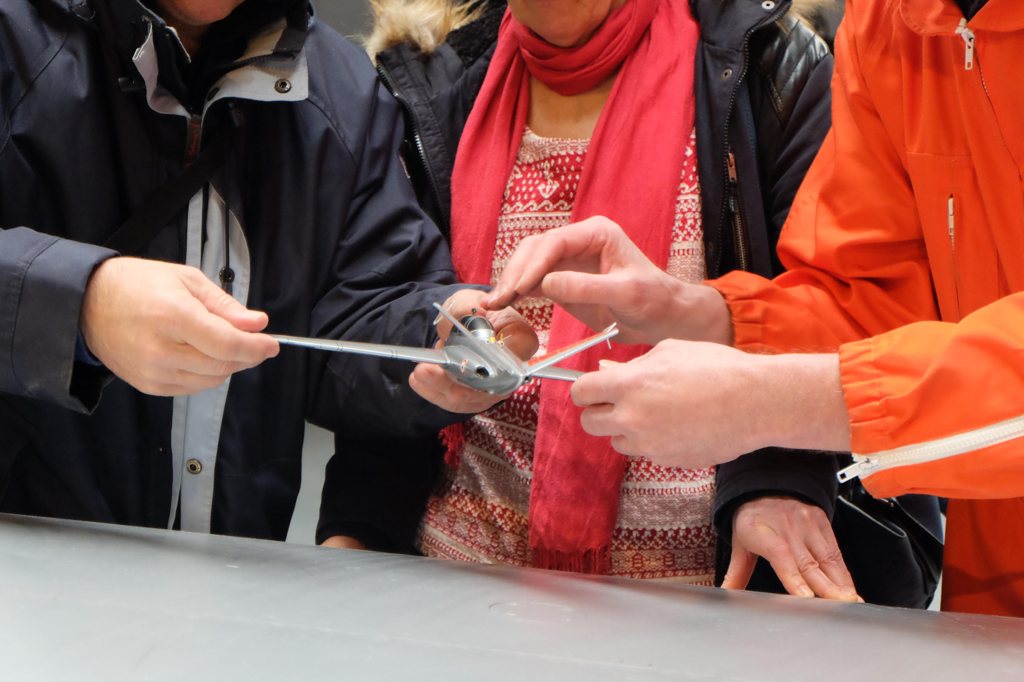 Les mains d'un Miraud guident celle d'un visiteur au musée Aeroscopia à Toulouse pour découvrir une maquette de 40 centimètres de Fouga magister.