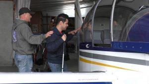 un jeune du centre Lestrade guidé dans sa découverte tactile du corps de l'avion