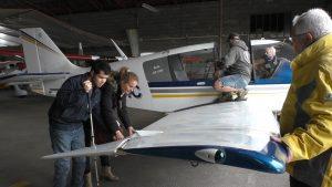 deux handicapés visuel explorent une aile d'avion dans un hangar à Nogaro