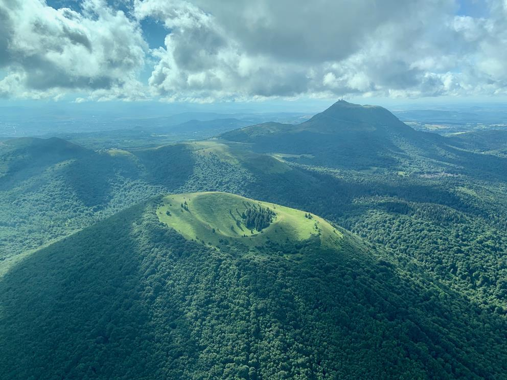 En vol vers Chambéry, les pilotes survolent le Puy de Côme, volcan de la chaîne des Puys. Du fait de la lumière s'infiltrant à travers les nuages, tout le massif semble en mouvement