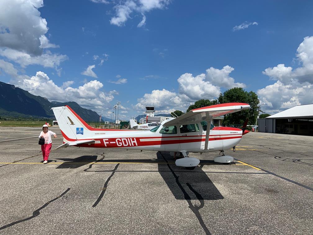 Un Cessna 172, blanc et rouge, aura accompagné nos pilotes durant cette semaine. Au départ ici de Chambéry, on le découvre de profil, au parking, sur un ciel assez dégagé