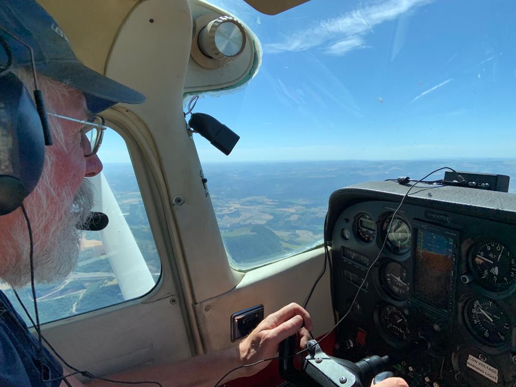 Ici, Patrice est aux commandes de l'avion. Depuis la cabine, le paysage, tout en ciel et verdure, atteste en arrière-plan d'une météo idyllique