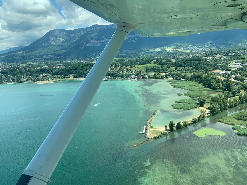 Un voyage varie les environnements: ici, un décollage depuis Chambéry survol la rive sud du lac. Le point de vue est circulaire, embrassant lac, rives boisées et massifs en arrière plan