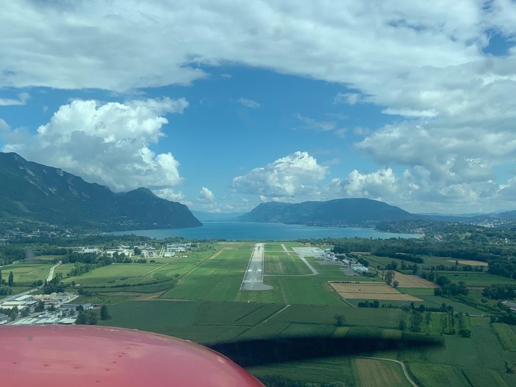 Vue frontal en plongée sur la piste d'atterrissage 36. On devine l'avant de l'avion, tandis que la piste en contre bas coupe l'étendue entre deux massifs encadrant un lac