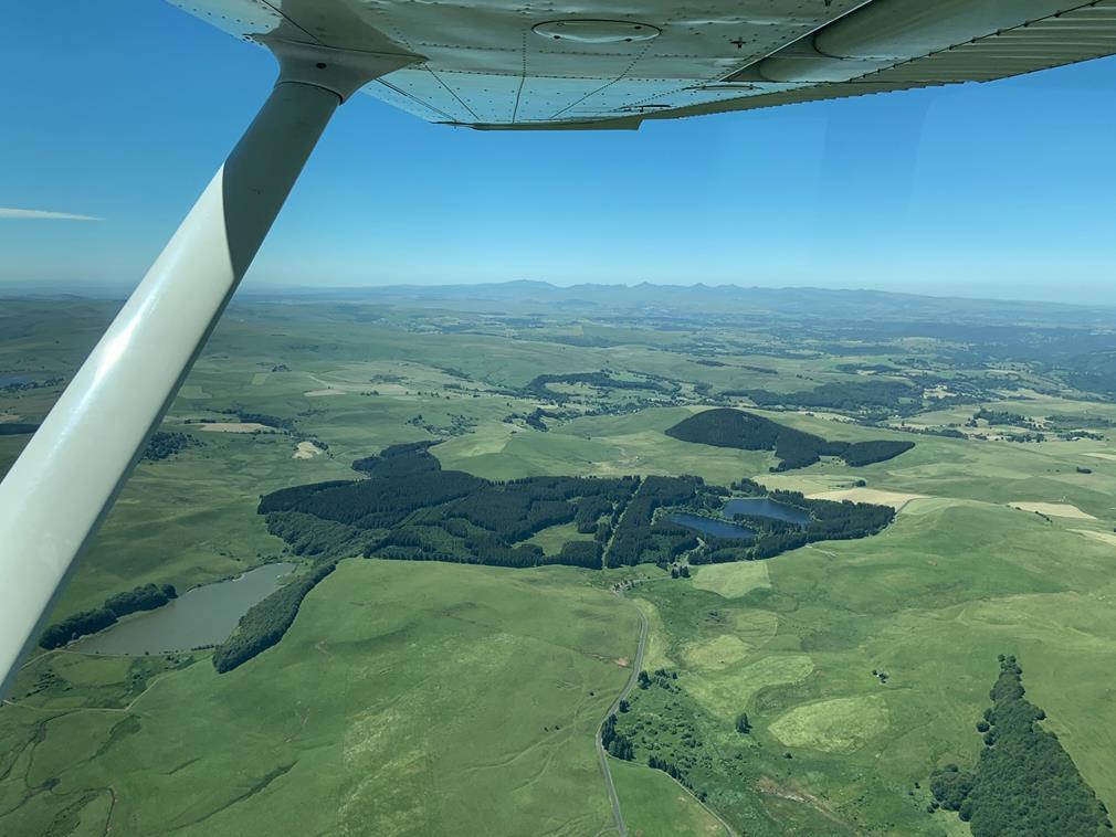Depuis le ciel, au-delà des ailes de l'avion au premier plan, des paysages comme le Cézallier ici offrent un spectacle grandiose: nuances de vert, dégradé de ciel bleu, nature à foison