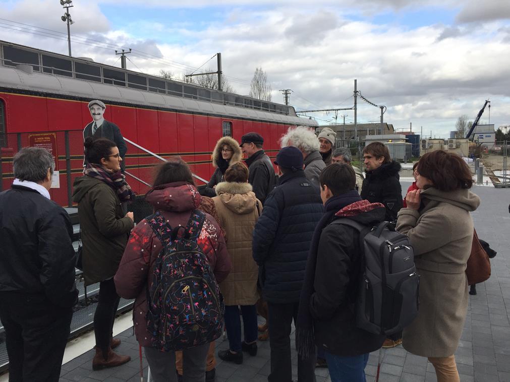 Encore à quai, le groupe de visiteurs s'apprête à monter dans le wagon postal, sous la houlette de leur guide