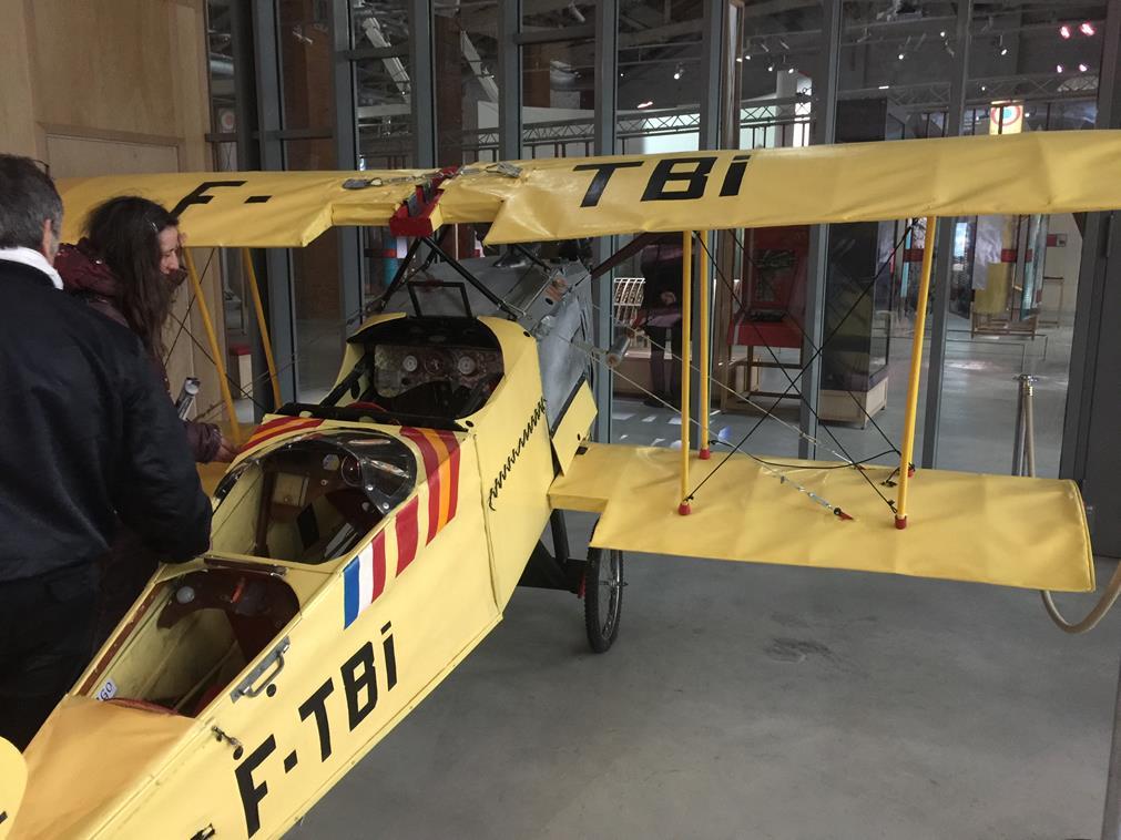 Chacun s'approche d'un petit avion postal jaune marqué F-TBi l'une des pièces du musée