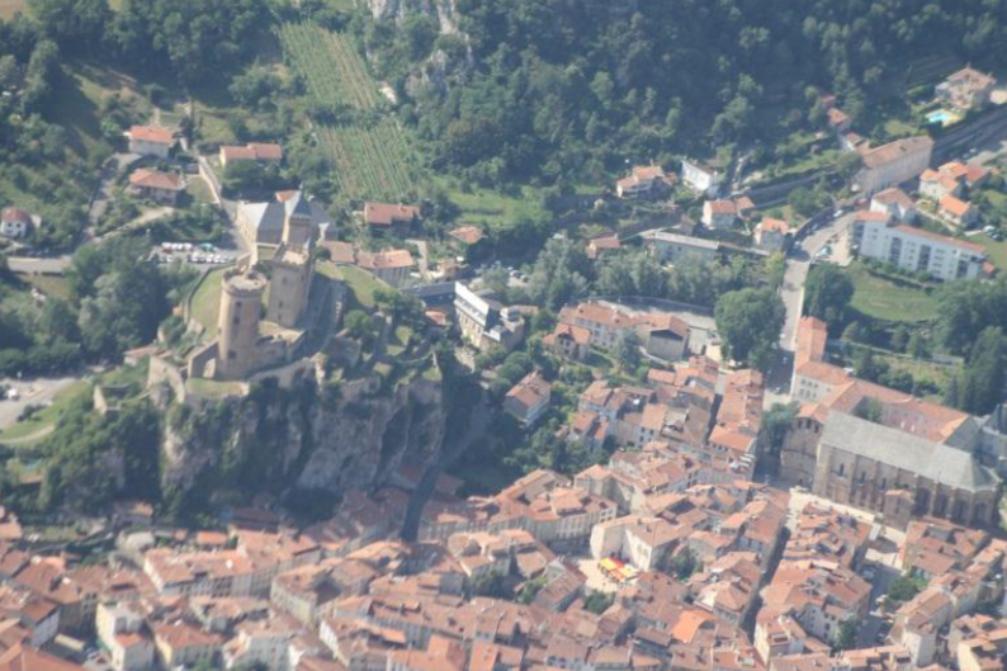 Grand point de vue aérien d'un des villages cathares survolés: les toits des maisons se mêlent aux anciennes fortifications entourées d'arbres