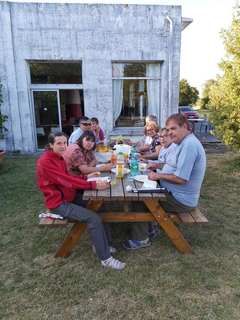La grande tablée du soir. En extérieur, l'ensemble des stagiaires profitent avec l'encadrement de la douceur estivale pour un repas convivial