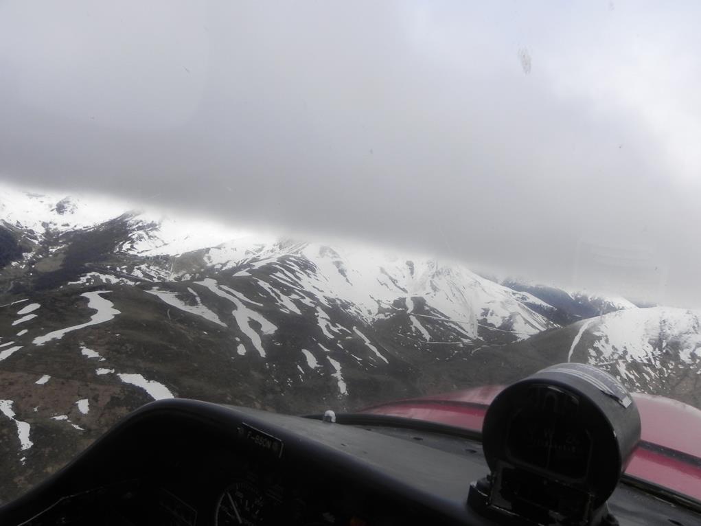 Chaîne des Pyrénées vue depuis l'avion: on distingue l'avant de l'avion et un peu du tableau de bord, devant les sommets enneigés de montagnes noires sur un ciel blanc