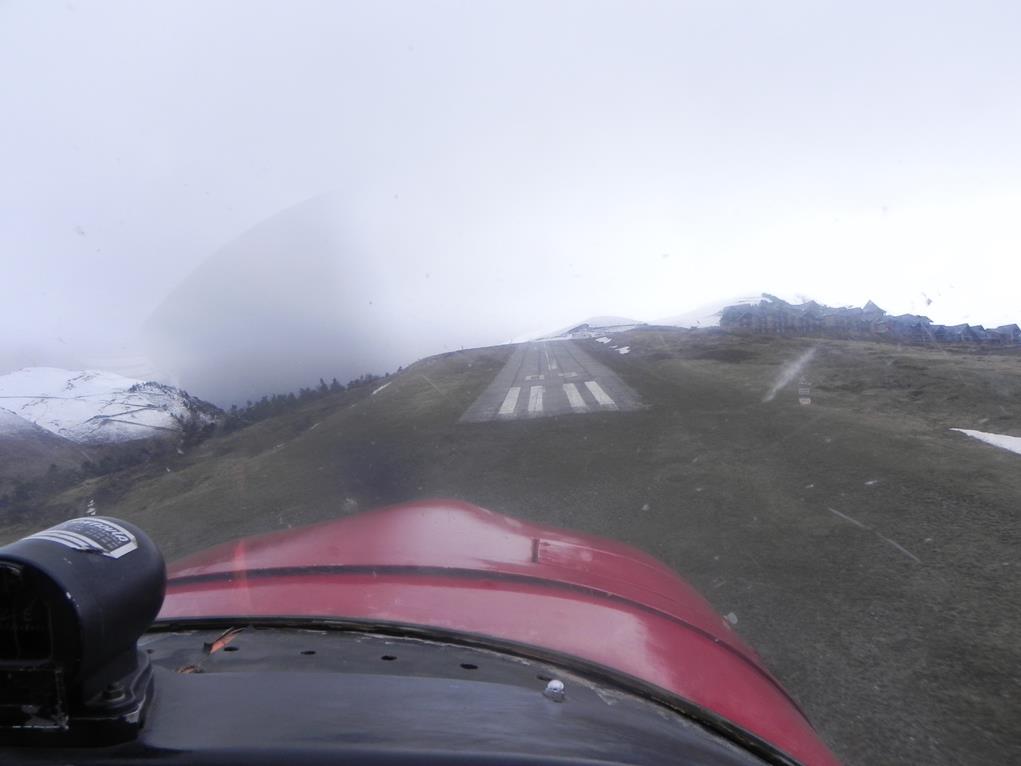 Piste d'atterrissage en approche : la piste, vue de face, encadrée par des montagnes enneigées, se perd dans le ciel blanc de neige en fond, tandis qu'on perçoit l'avant de l'avion prêt pour le final de ce vol
