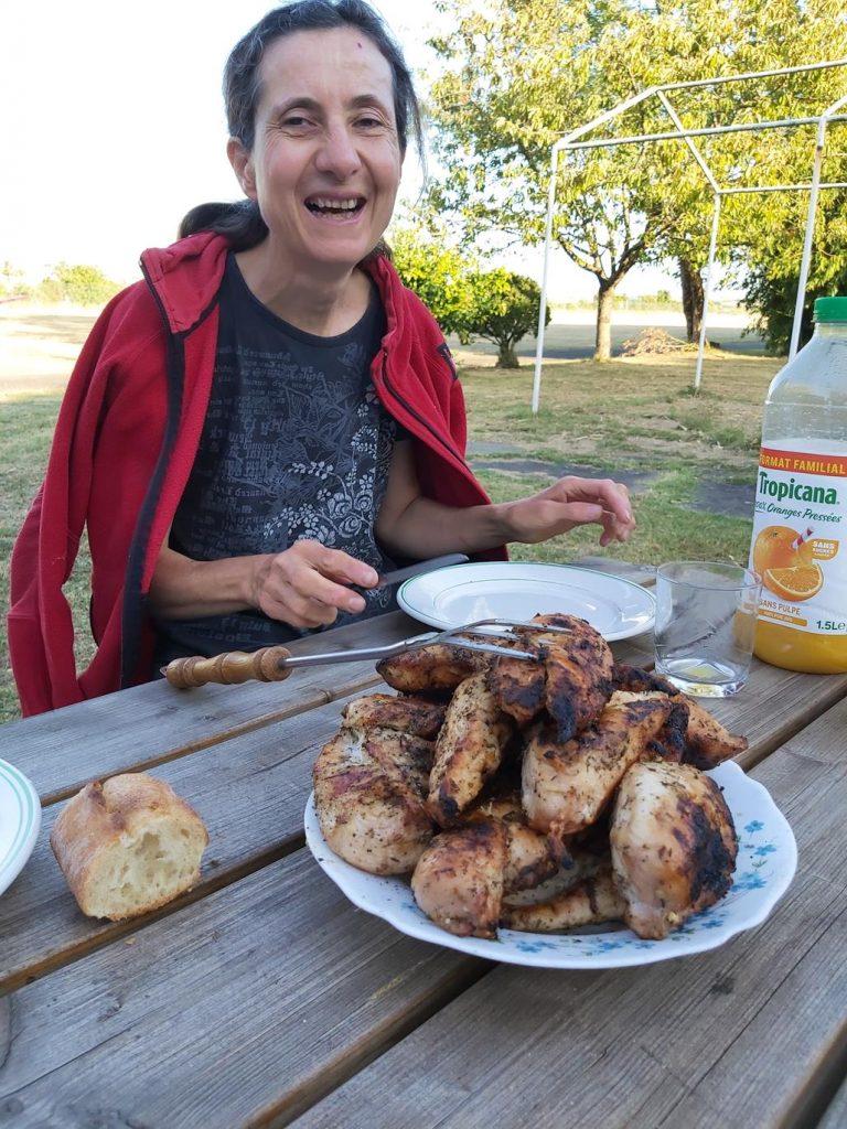 Isabelle, tout sourire, à table, devant une énorme quantité de poulet rôtis au barbecue