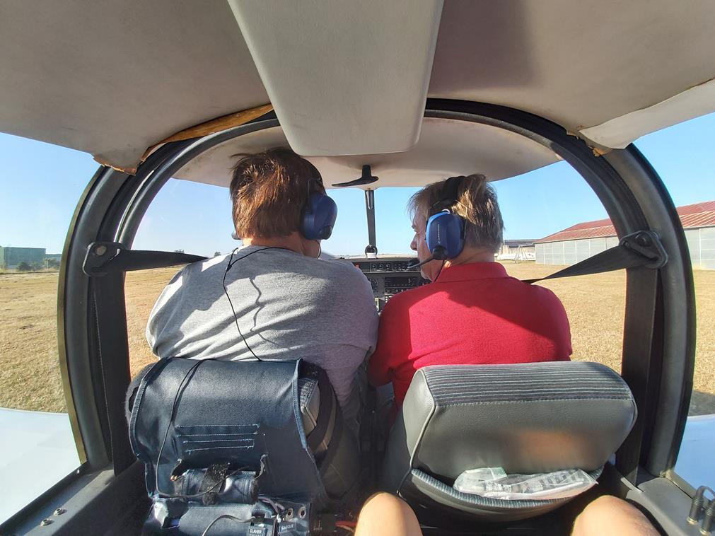Vus depuis la place arrière de l'avion, Patrice et Alex sont tous les deux à l'avant, prêts à décoller à bord de cet appareil encore au parking pour les séquences d'apprentissage