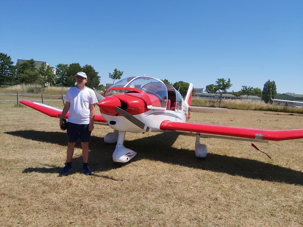 Quentin pose fièrement devant son avion au départ. Sur la piste, le rouge de l'avion se détache sur le ciel présentant une météo idéale