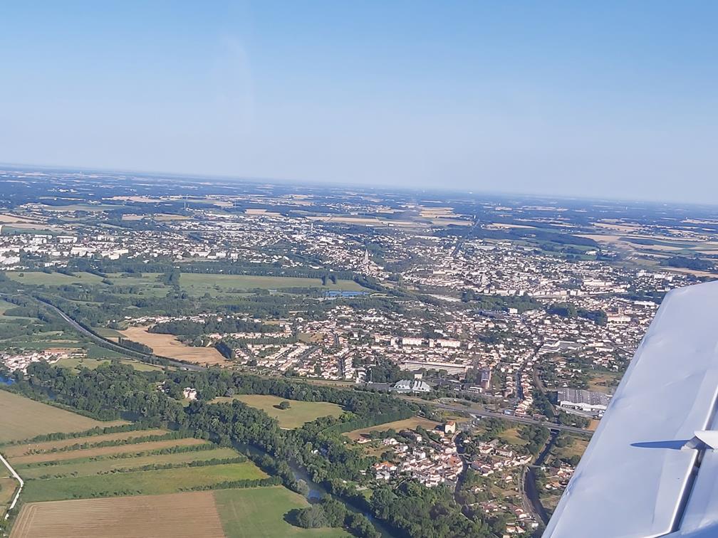La ville de Saintes vue depuis l'avion en vol : on aperçoit l'aile de l'appareil dans le coin inférieur droit, tandis qu'une concentration de toits se découpent au milieu des champs sur un horizon parfaitement dégagé