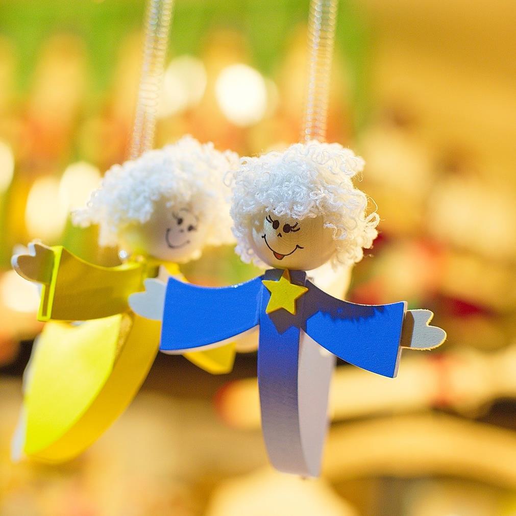 Gros plan de deux anciens jouets en bois représentant deux anges suspendus, les bras ouverts, le sourire aux lèvres. Une revisite artistique du saut de l'ange sur fond d'éclairage tamisé