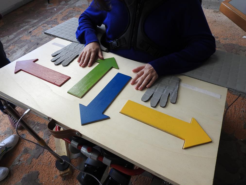 Vue du dispositif touchtab: les mains de l'utilisateur sont posées à plat sur une table ; cette dernière est recouvertes d'éléments en légers reliefs: l'empreinte des deux mains puis quatre flèches : l'une se dirigeant vers l'utilisateur, l'autre devant lui, puis deux désignant les côtés.