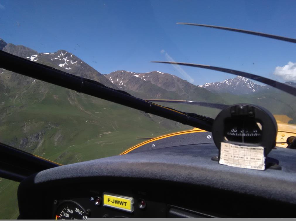 Vue depuis le poste de pilotage: à hauteur de tableau de bord, l'avant de l'avion est visible tandis que s'étendent les montagnes légèrement saupoudrées de neige en haute altitude, la verdure occupant leurs pieds.