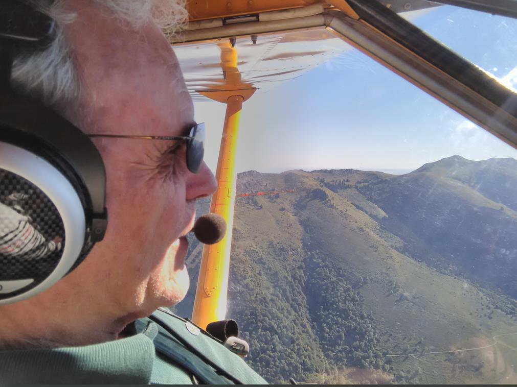 """De profil, Jean-Claude est tout sourire à son poste de pilotage, sur fond de monts verts, de ciel bleu et un bout de l'aile de l'avion. Il est en plein échange avec la fameuse """"voix"""" à l'aide de son micro."""