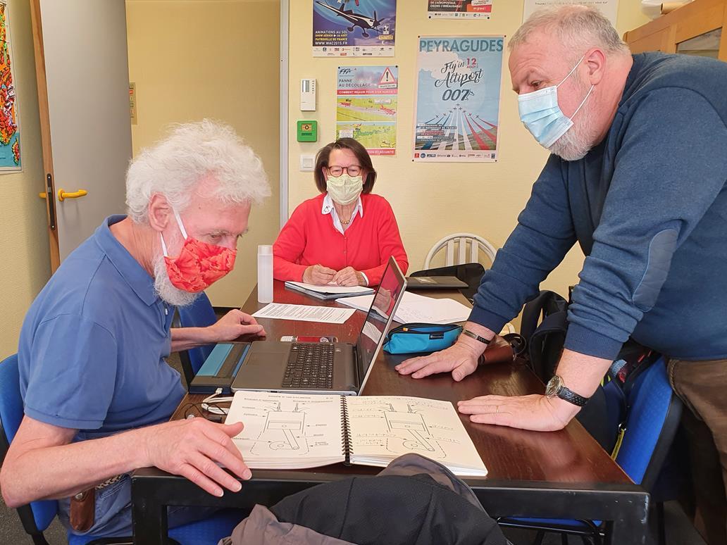 Autour d'une table de réunion, Odile, Patrice et Philippe travaillent au projet: sous leurs mains, des cahiers de schémas relatifs à ce pilotage adapté.