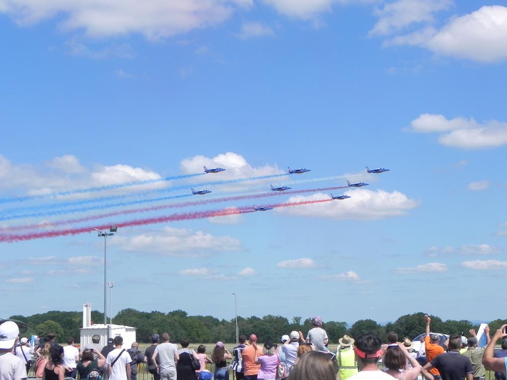 Au premier plan, le public, de dos, suit la démonstration de la patrouille de France ; cette dernière, au second plan et occupant la moitié supérieure de l'image, traverse le ciel de gauche à droite : sept avions laissent des trainées bleu, blanc, rouge dans un grand ciel bleu.