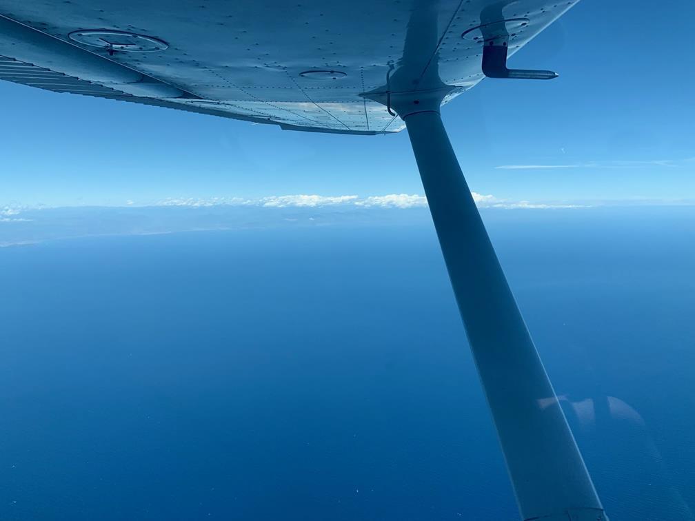 Symbole d'une météo enchanteresse, on pourrait presque douter de la présence de la Corse, au-delà de l'étendue bleue et au bout de l'aile du Cessna. Tout en haut de l'image, le ciel rencontre la mer dans une même couleur, juste départagée par les contours de l'île de Beauté.