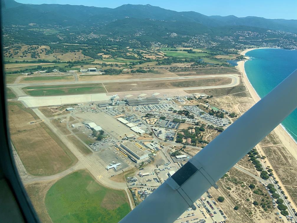 L'aéroport d'Ajaccio : sur un fond de montagnes vertes, la piste touche presque la mer qui borde l'intégralité du lieu. Des avions sont à l'arrêt, à côté de parkings bien remplis.