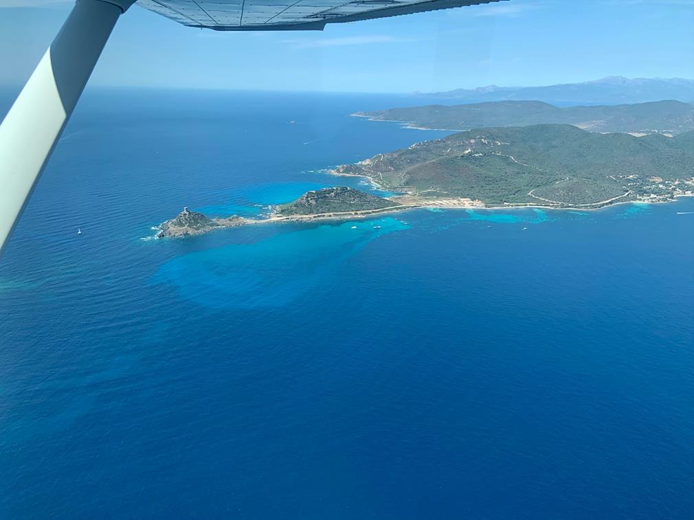 La pointe des îles Sanguinaires ; un point de vue paradisiaque. Le bras de terre s'avance sur un eau au bleu profond et va en s'étirant pour avancer dans la mer. L'île est recouverte de verdure. A sa pointe, on distingue une ancienne construction de pierres, ruines ou phare.