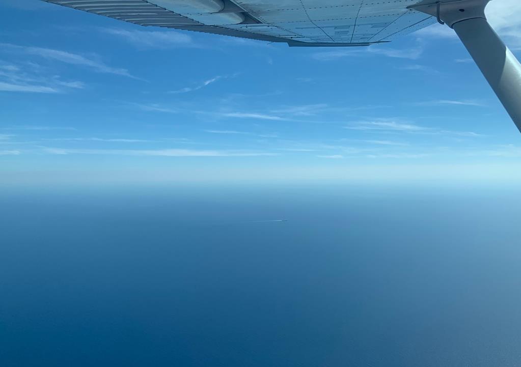 En vol au-dessus de la méditerranée, un ferry, seul et tout petit au loin, travers un bleu faits de nuances lumineuses. La trainées d'écume qu'il laisse derrière lui semble imiter les quelques fils de nuages blancs dans un ciel dont on ne devine pas le point de rencontre avec la mer.