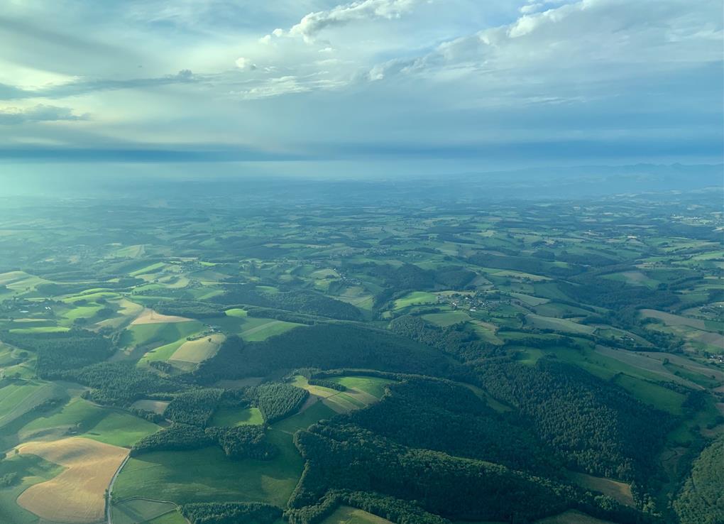 Aperçu de cette météo chargée: le cantal s'étend sous un horizon très sombre, les nuages gris et dense projettent des ombres sur les champs.