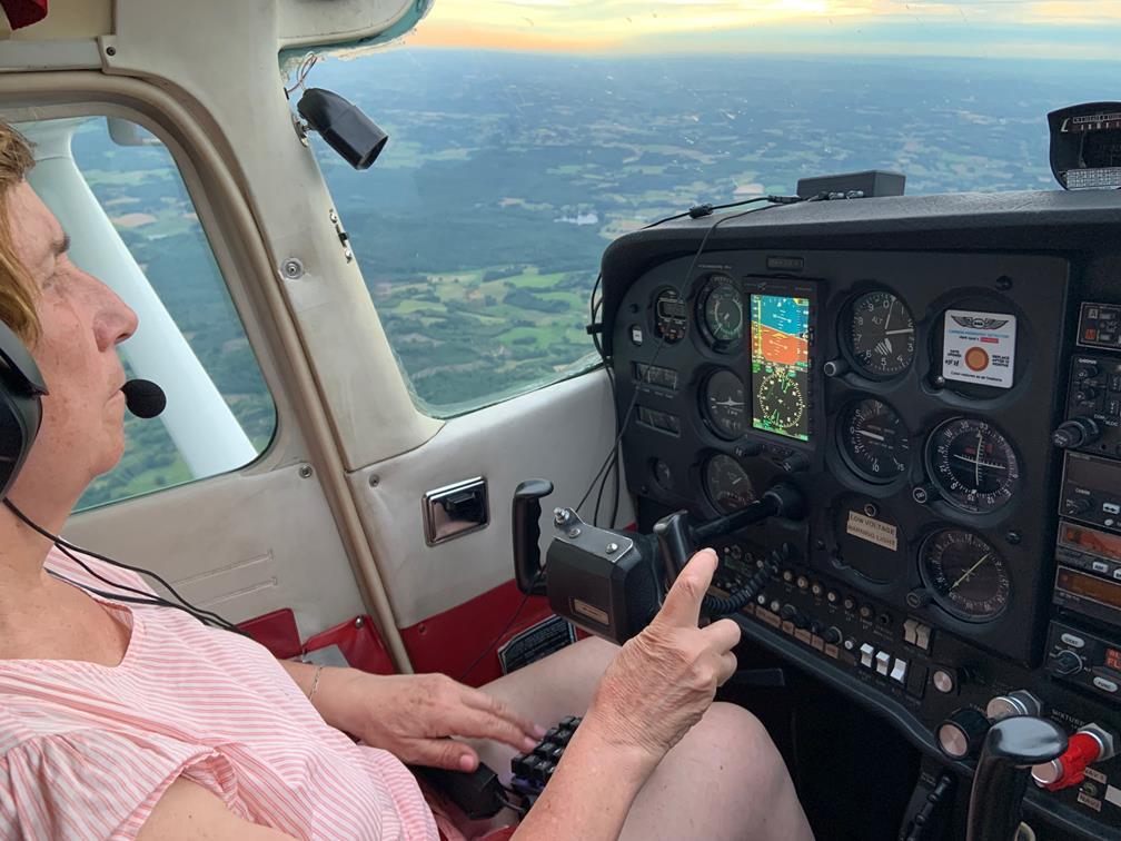Chantal aux commande, de profil, sur un ciel orange et jaune au-dessus des monts.
