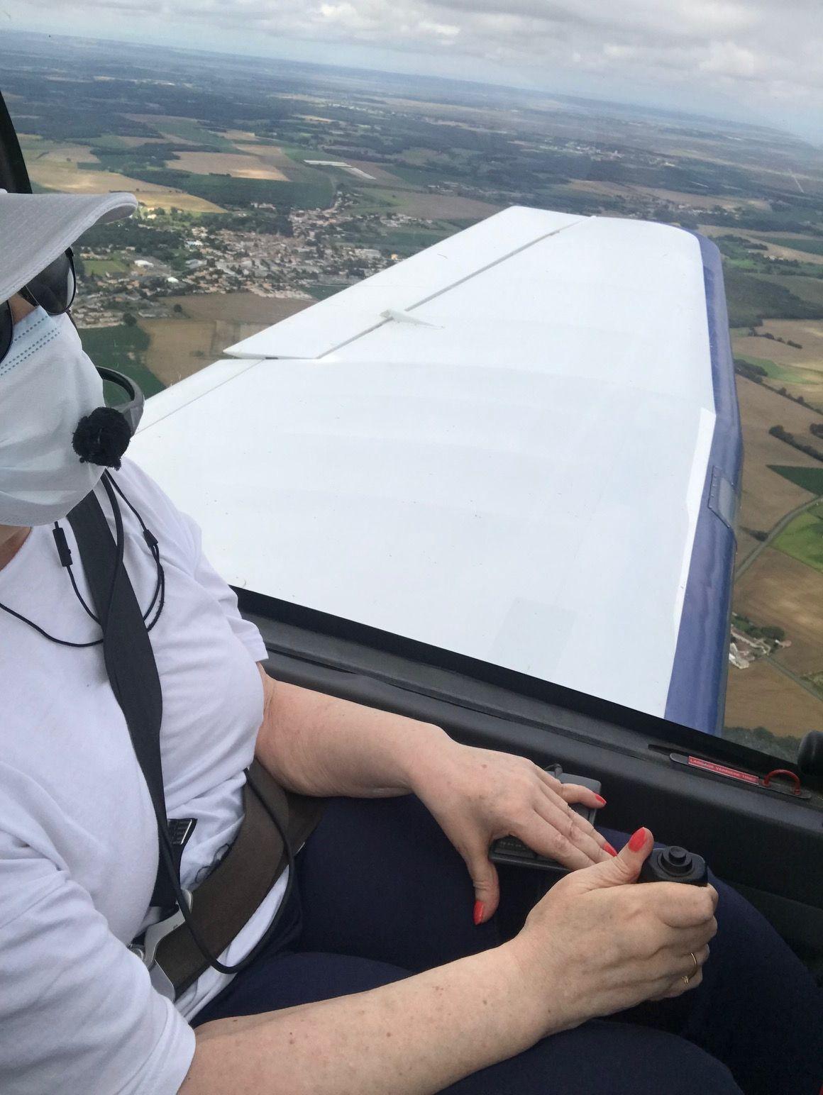 Catherine en vol, les mains sur les commandes ; la partie haute de l'image est occupée par l'aile de l'avion tandis qu'on profite de l'horizon de verdures et d'un morceau de ciel